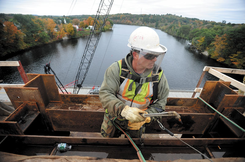 WORK IN PROGRESS: Bud Greene, an iron worker with Reed and Reed, prepares to secure a temporary brace atop the one standing arch of the new Norridgewock bridge last week.