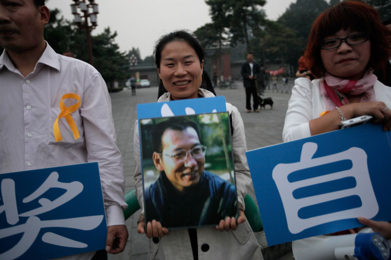 Supporters of Liu Xiaobo holding his picture gather outside a park in Beijing Friday, Oct. 8, 2010. Imprisoned Chinese dissident Liu won the 2010 Nobel Peace Prize on Friday for using non-violence to demand fundamental human rights in his homeland. The award ignited a furious response from China, which accused the Norwegian Nobel Committee of violating its own principles by honoring