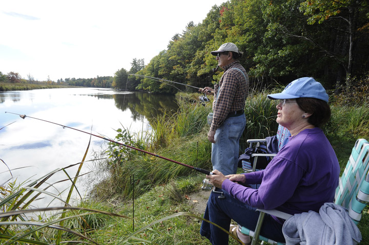 Retirees Barbara and Sal Moscato from Brunswick enjoy one of the last few fishing days today, sitting on the banks of the Muddy River in Topsham to catch a few.