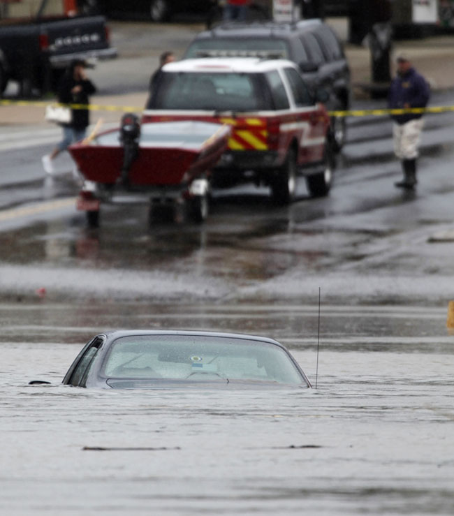 A car is submerged in floodwater in Darby, Pa., today.