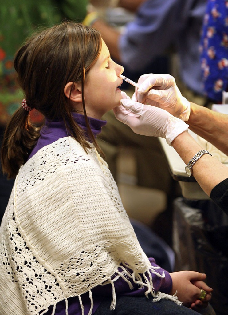 Kate Friberg, 8, of Cape Elizabeth gets a second dose of H1N1 flu mist at a clinic at the Cape Elizabeth Fire Station on Tuesday. Vaccine doses are readily available in Maine, even to healthy adults.