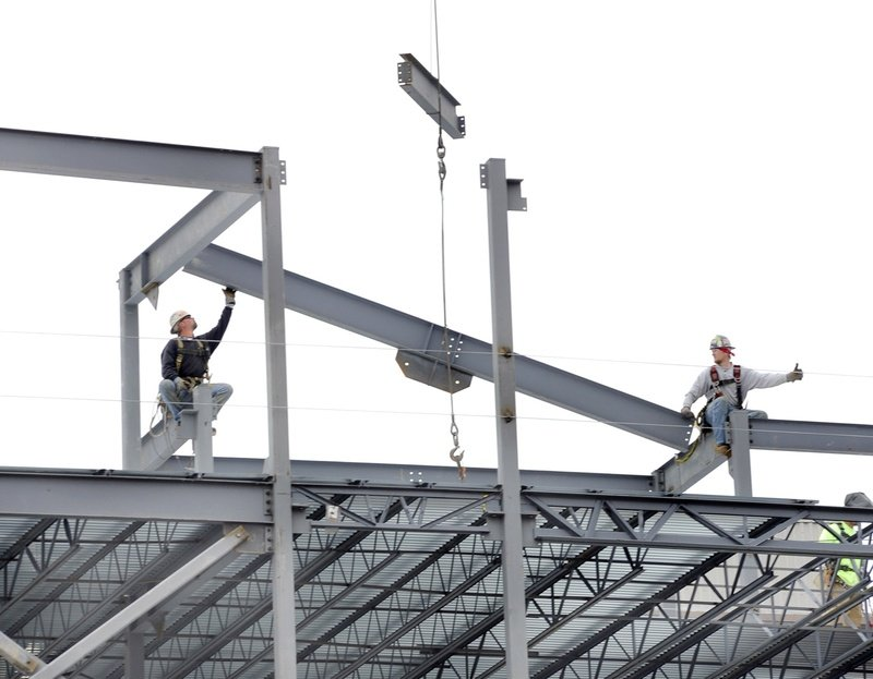 Iron workers connect steel beams on a hotel, restaurant and condo project, part of a recent surge in  commercial projects in Portland.