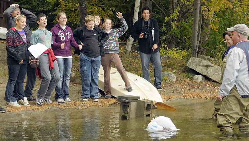China Middle School students cheer as their boat finally sinks after Jobs For Maine's Graduates Chief Operating Officer Craig Larrabee, far right, put another brick on top of it on Wednesday morning. Their boat was made from a plastic bag, a round pool noodle, milk jugs and twigs — part of the junkyard regatta portion of a training program at the YMCA Camp of Maine in Winthrop.