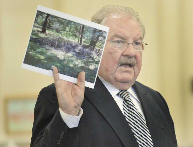 Defense attorney Daniel Lilley holds a photograph of the site where Kelly Gorham s body was buried in New Hampshire while addressing the jury during closing arguments in the murder trial of Jason Twardus on Thursday.