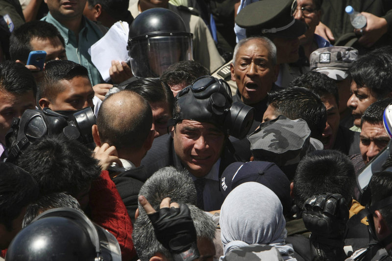 Ecuadorean President Rafael Correa, center, wearing a gas mask, is caught in a police protest Thursday at a barracks in the capital of Quito. The government declared a state of siege after rebellious police left Quito and other major cities unprotected in a nationwide strike. Looting was reported in the capital and two banks were sacked.