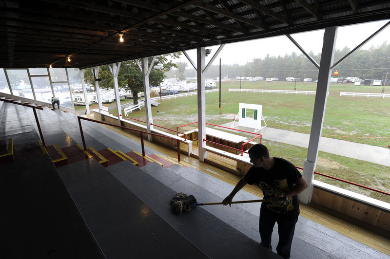 Jake Townsend and his mother Judy Townsend clean the hog and goat grandstand as they and a multitude of other workers get ready for the Fryeburg Fair, which opens on Sunday.