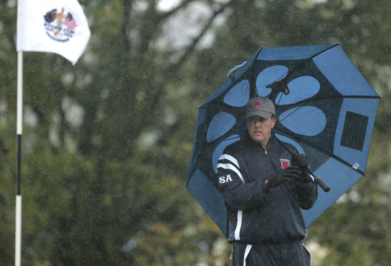 Phil Mickelson takes shelter under an umbrella Friday, when heavy rains soaked the course and forced suspension of play for more than seven hours at the Ryder Cup. As a result, none of the early fourball matches was completed.