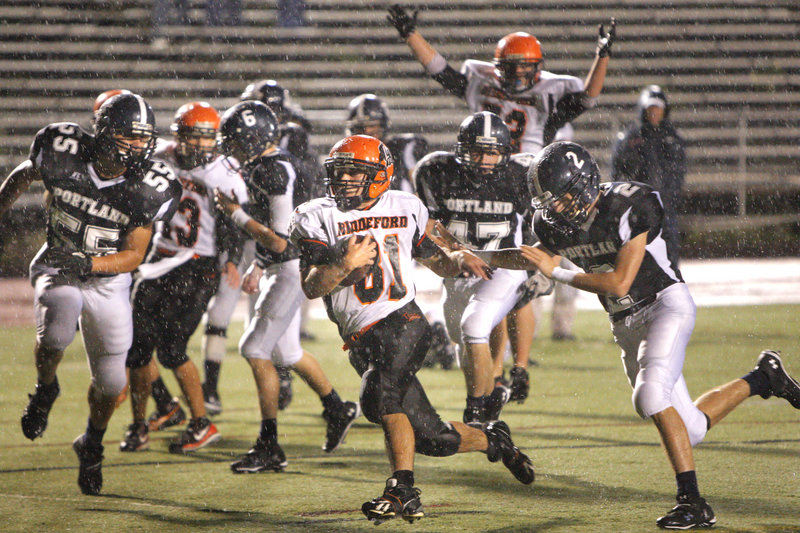 Amid the raindrops at Fitzpatrick Stadium on Friday night, Ryan Webb of Biddeford scurries into the end zone to complete a 31-yard run in the third quarter and give the Tigers a three-touchdown lead against Portland. Biddeford went on to a 35-7 victory.