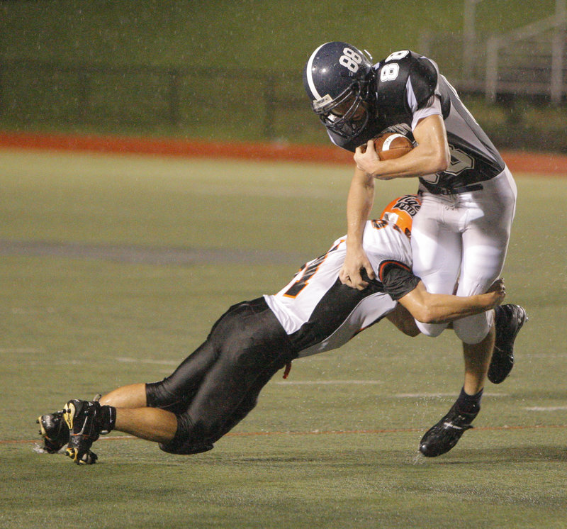 Mike Herrick, who scored only touchdown for Portland on a kickoff return, is brought down down by Ryan Webb of Biddeford in the open field.