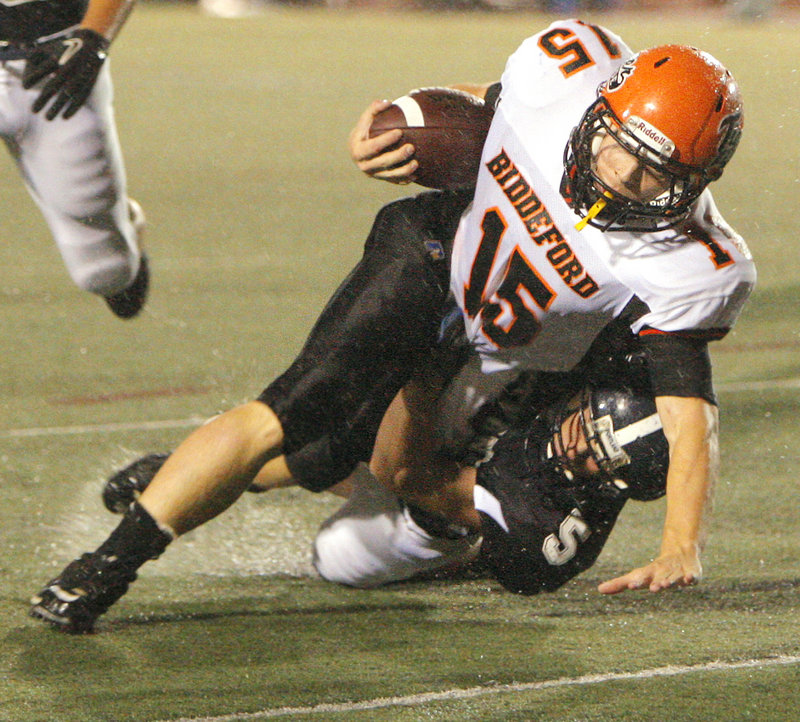 Biddeford quarterback Tyler Audie strains for balance Friday night while being brought down by Gary MacDonald of Portland. Audie sparked the Tigers to a 35-7 victory at Fitzpatrick Stadium.