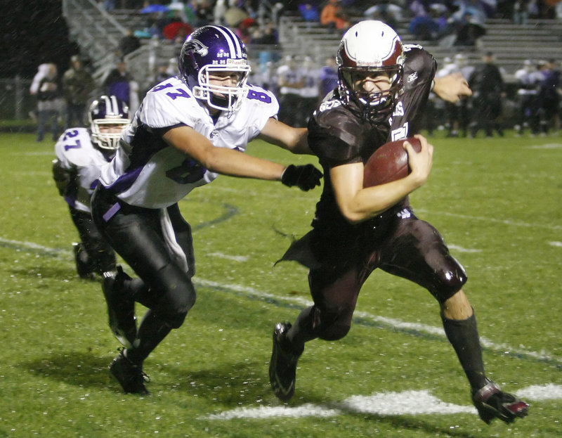 Cody Laberge, right, of Windham tries to elude Jack Verrill of Marshwood and head downfield. Laberge scored four touchdowns for the Eagles.