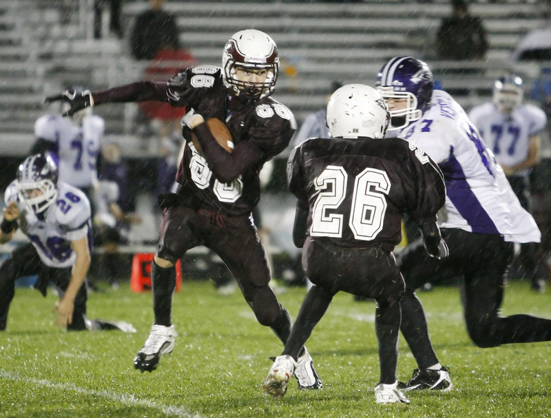 Drew Gagnon, left, of Windham sets up a block by Damien Sheppard on Marshwood's Jack Verrill and tries to turn the corner during Windham's 35-6 victory Friday night.