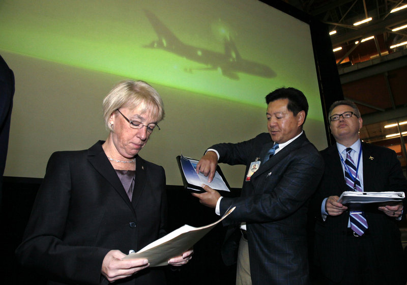 Sen. Patty Murray, D-Wash., left, goes over her notes as she stands with Boeing officials before a rally at Boeing's production facility in Everett, Wash., last week. She has improved her standing in the polls of late and Democrats have set aside money for advertising if she needs it.