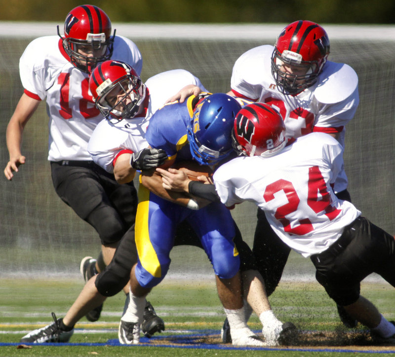 ABOVE: Falmouth quarterback Zach Alexander is on his own Saturday as the Wells defenders reach the backfield. Helping to gang-tackle Alexander are Brandon Pridham, 18, J.T. Sherburne, Joey Spinelli, 24, and Josh Ingalls, 83. Wells had few problems in rolling to a 41-8 victory on the road. BELOW: As the offensive line clears the way, Caleb Bowden of Falmouth runs through a huge hole in the first half. The Yachtsmen were only able to total 103 yards and nine first downs, however, and suffered a second consecutive loss.