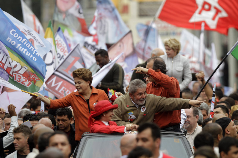 From the top of a vehicle, President Luiz Inacio Lula da Silva, right, Workers Party presidential candidate Dilma Rousseff, left, and first lady Marisa Leticia, bottom, wearing a red hat, greet supporters during a campaign rally in Sao Bernardo do Campo, Sao Paulo state, Brazil, on Saturday. Brazil will hold general elections today.