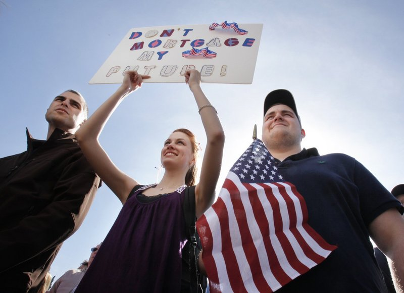 Corey Thompson of Spruce Head, Rebecca Harper of Cushing and Jacob Harper of Cushing listen to speakers at a tea party rally in Boston earlier this year. The sign reads