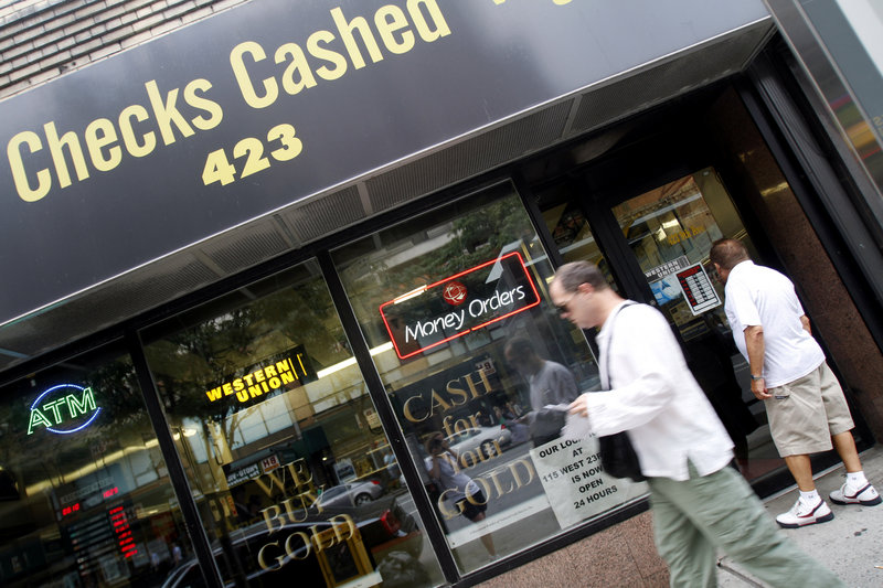 A man looks into the UBNY check-cashing store as another walks past, in the Hell's Kitchen neighborhood of Manhattan in New York last August. A federal study last year found that about one in four U.S. households skirts banks and relies on services such as check-cashing and payday loans.