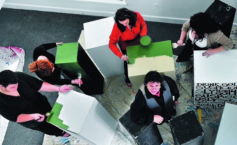 Sallie McCorkle looks up Sunday as University of Maine at Farmington students begin painting pieces that will become a multi-level art exhibit that opens Thursday at the UMF Art Gallery. From left are Nick Lorenzen, Kayla Currier, Katie Steward and Heidi Bryant.