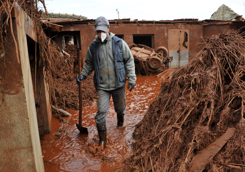 A villager walks through his yard flooded by toxic mud in Kolontar, Hungary, on Tuesday. At least four people have died in flooding caused by the rupture of a red sludge reservoir at an alumina plant in western Hungary.