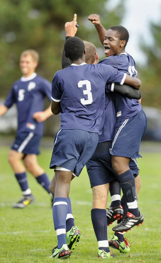 Ralph Houanche, right, of Portland celebrates with Abde Ahmed, 3, and another teammate after scoring in the first half of a game Tuesday against Cheverus. The goal stood up for a 1-0 victory.