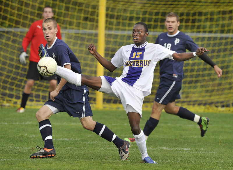 Raphael Tshamala of Cheverus knocks down a pass in front of Portland's Brett O'Kelly, left, and Feliks Cobanovic during the Bulldogs' 1-0 boys' soccer victory Tuesday.
