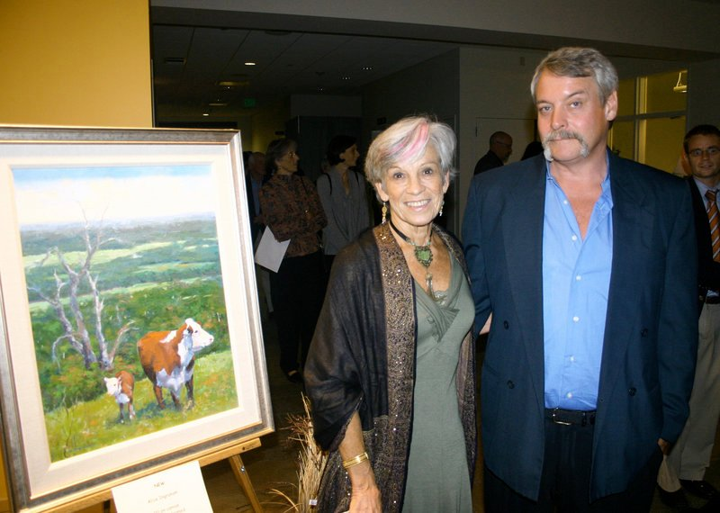 "Artist Alice Ingraham and her husband, Craig Hurd, stand next to her piece in the art auction titled ""New."""