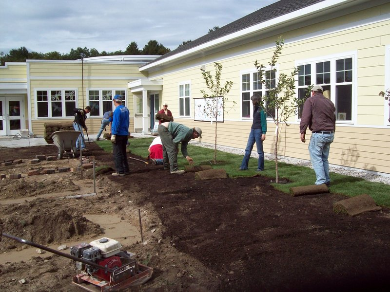 Volunteers work around fruit trees that have been planted, spreading compost in some areas and sod in others at Morrison Developmental Center in Scarborough. The center provides assistance to adults with developmental disabilities. The food grown in the new garden willbe used in the center's kitchen and in group homes, and the excess donated to soup kitchens.