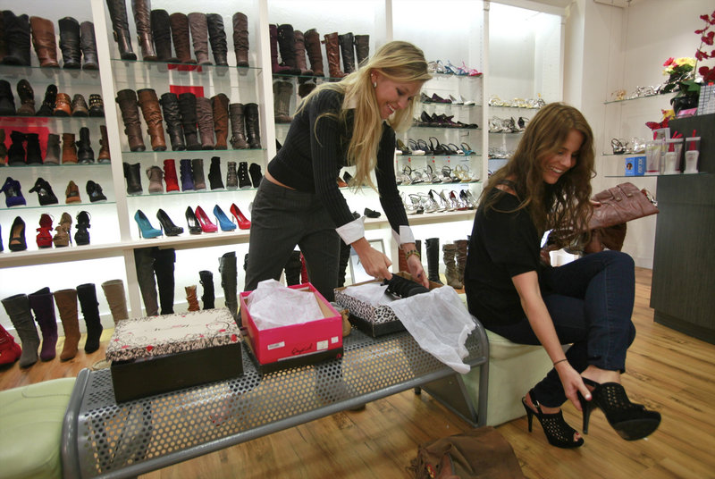 Dino James, left, and Emily Jones try on shoes this week at a Weiman Shoes store in Los Angeles. Retailers are reporting surprisingly solid sales gains for September, boosted by back-to-school shopping in the first half of the month.