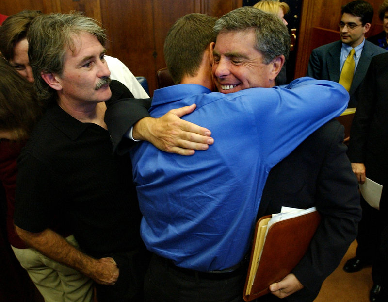 Attorney Robert Sherman, right, is hugged by church abuse victim Gary Bergeron, center, and thanked by victim Bernard McDaid after the Boston Archdiocese agreed to settle clergy sex abuse cases on Sept. 9, 2003. In the wake of the abuse scandal, more churches are doing background checks.