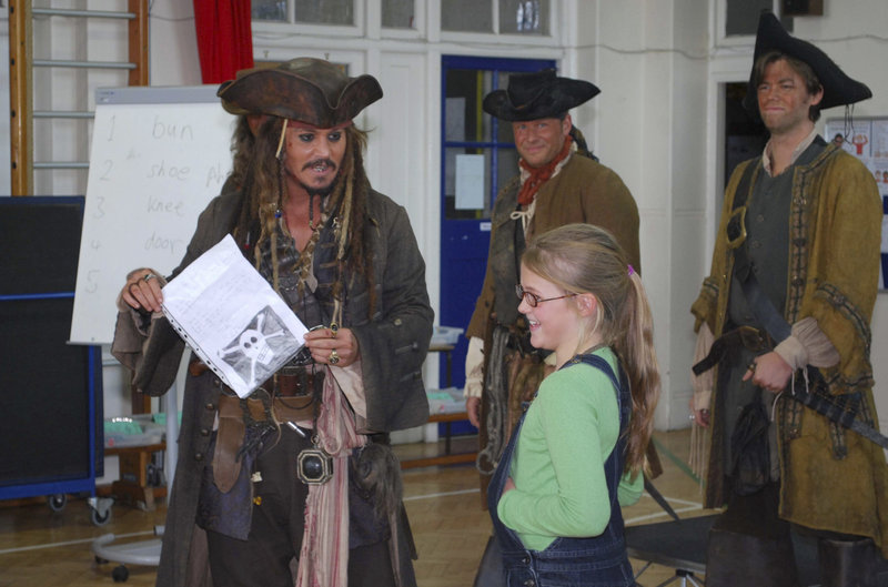 "Actor Johnny Depp, left, holds a letter from 9-year-old Beatrice Delap, right, inviting him to attend her Meridian School assembly. Depp, dressed as his character Jack Sparrow from the ""Pirates of the Caribbean"" movie series, is currently filming the latest installment nearby."