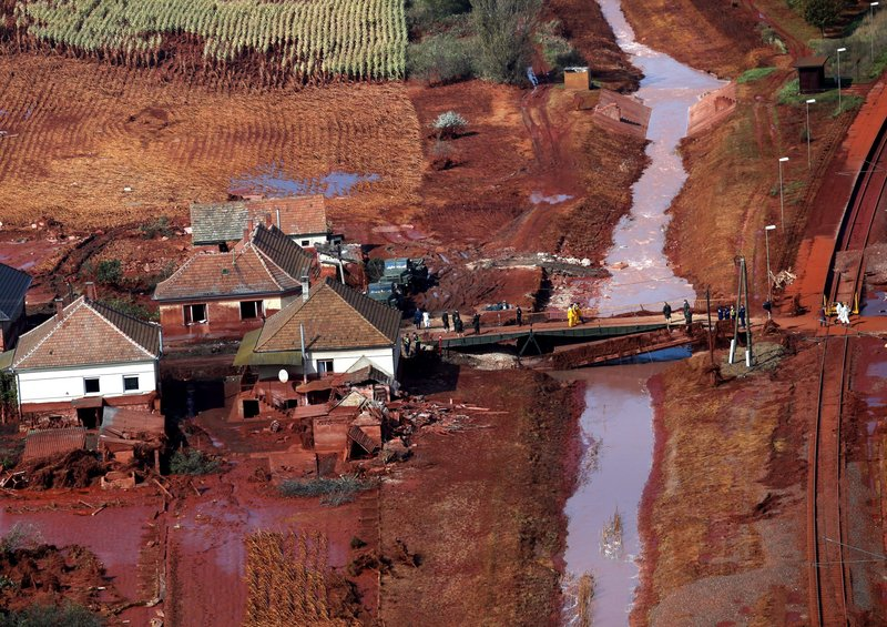 An aerial view shows rescue team members crossing a pontoon bridge that replaces one washed away by a sludge flood in Kolontar, Hungary, on Friday, after the dike of a reservoir containing red sludge from an alumina factory in nearby Ajka broke early this week. Rescuers also found two more victims from Hungary's ecological disaster, bringing the death toll to seven.