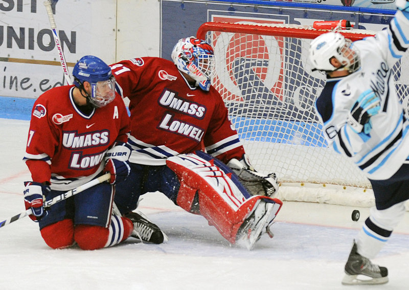 UMass-Lowell defenseman Maury Edwards, left, and goalie David Carr watch as the puck slides into the goal after Adam Shemansky of Maine's shot in the first period Friday night. The Black Bears won their opener, 8-2.