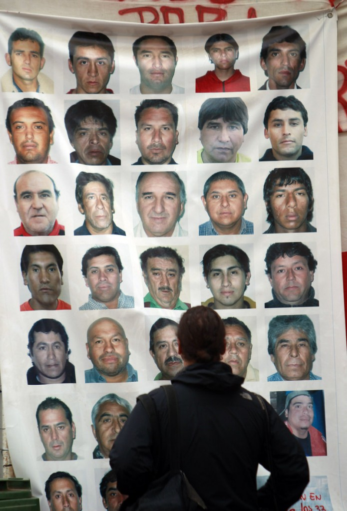 A journalist looks at a banner Friday with images of the 33 trapped men at the San Jose Mine in Copiapo, Chile.