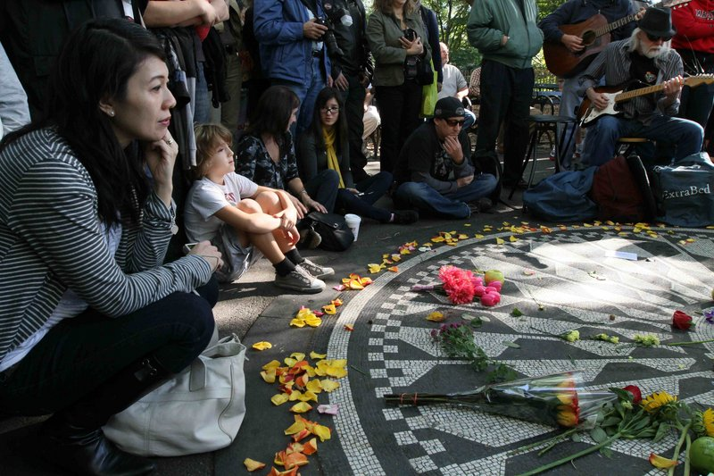 """Janice Tong, left, of Sydney joins fans paying tribute to John Lennon on Saturday in New York's Central Park. """"I think the mourning is over for John,"""" said his ex-wife, Cynthia, in England. """"I think it's time to celebrate."""""""
