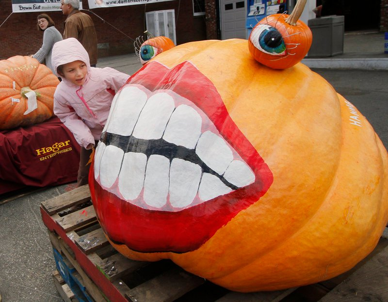 Rebecca Packard, 8, of Durham takes a look at a pumpkin decorated by Hannah Boone.