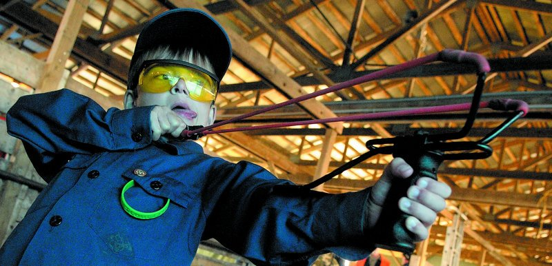 Dan Macolini of Kennebunk takes aim at the slingshot range during ScoutFest on Saturday at the Windsor Fairgrounds. The festival featured traditional Scouting activities like the pinewood derby, along with a new twist: a technology center.