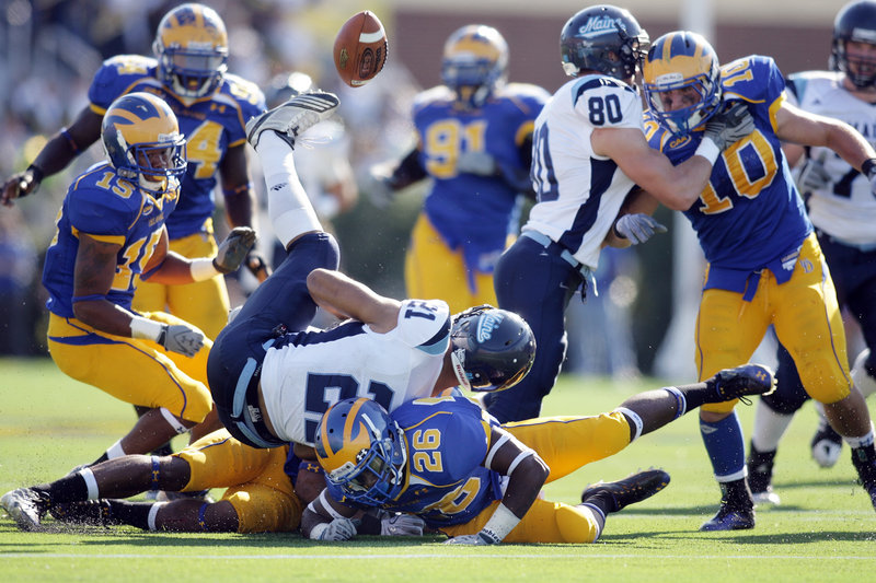 Maine running back Jared Turcotte (21) loses the ball as he s hit by Delaware defensive backs Anthony Bratton, behind, and Ricky Tunstall (26) in the fourth quarter of Delaware s 26-7 victory Saturday at Newark, Del.