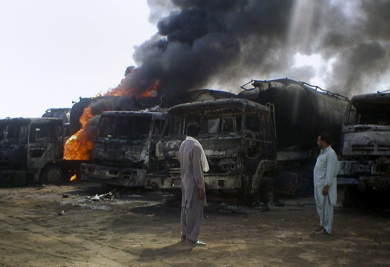 Local residents look at burning oil tankers after a militant attack in Mithri, about 120 miles east of Quetta, Pakistan, on Saturday. Gunmen armed with a rocket torched 29 NATO oil tankers in southwestern Pakistan before dawn Saturday.