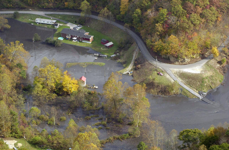 In this Oct. 16, 2000, photo, houses at Coldwater Fork sit along some of the 300 million gallons of coal slurry that spilled from a 68-acre retention pond upstream after the bottom fell out several days earlier, blackening 100 miles of waterways.