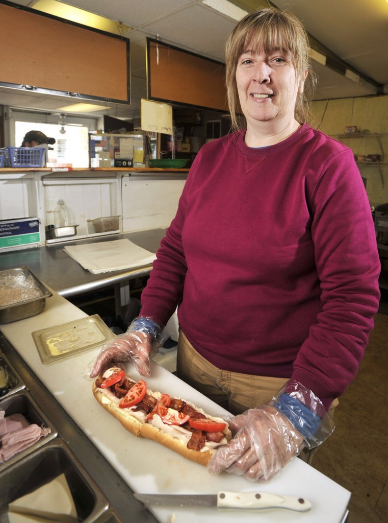 Deb Carter, owner of Deb s Sandwich Shop in South Portland, prepares lunch for a customer.