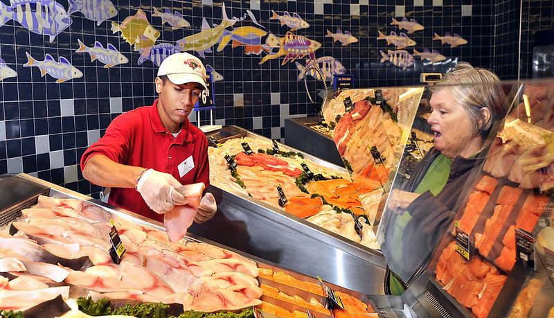 Nabil Sibouih, an assistant seafood manager at Hannaford, helps regular swordfish customer Carol McCracken of Portland pick a swordfish steak from Linda Greenlaw's catch.