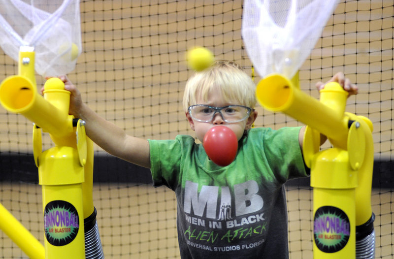 Nicholas Moulton has both hands full as he fires foam-ball cannons inside the new Extreme Family Entertainment Center in the Maine Mall in South Portland.