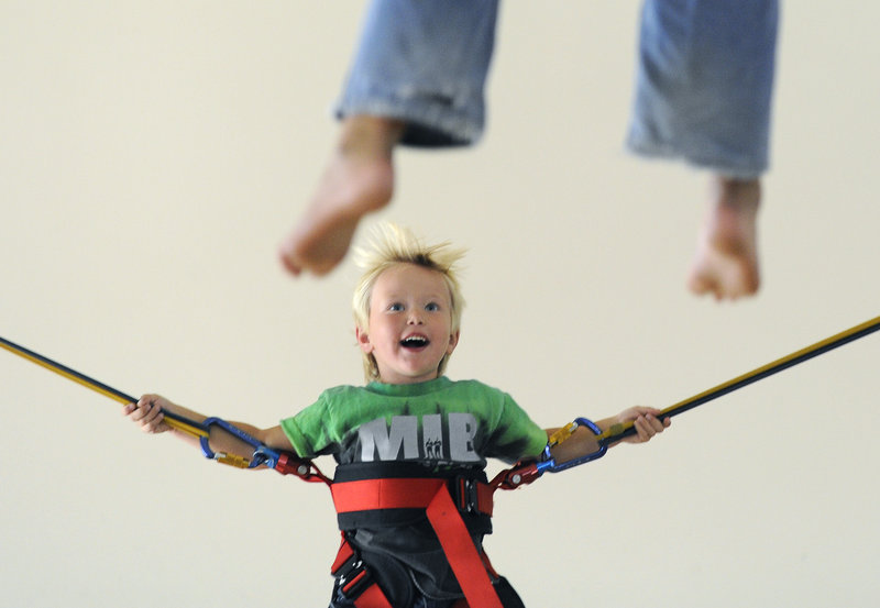 Nicholas Moulton, 4, of New Gloucester tries out the bungee-jumping trampoline at the new Extreme Family Entertainment Center, set up in the former Linens 'N Things space at the Maine Mall in South Portland.