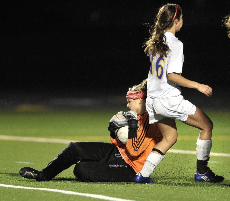 Yarmouth goalie Olivia Smith makes sure to control the ball as Jesse L'Hereux of Falmouth waits for a rebound that never came during their scoreless tie Tuesday.