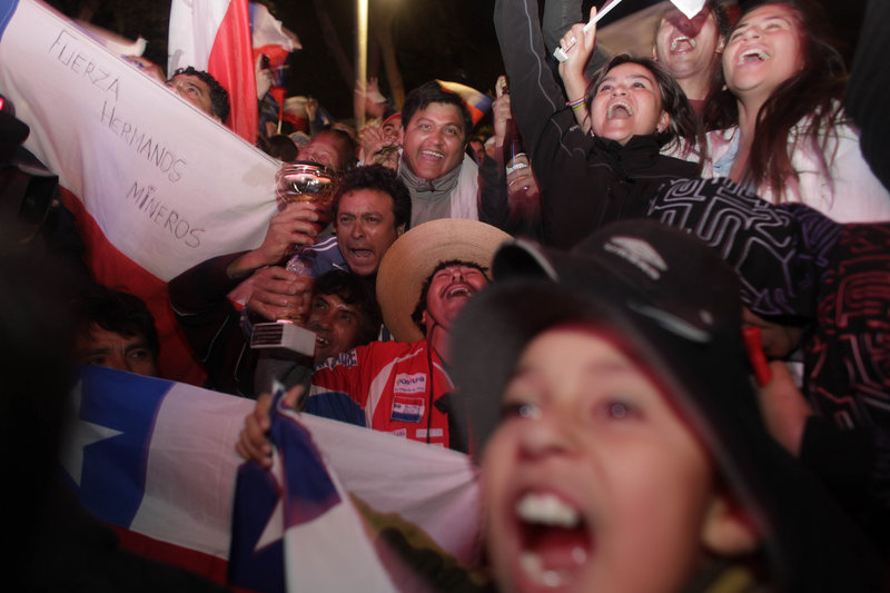 People celebrate at a camp outside the San Jose mine near Copiapo, Chile, as they watch on a giant TV screen as Florencio Avalos emerges to safety.