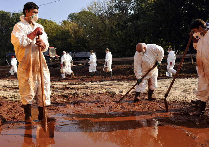 """Volunteers wearing protective clothing clean toxic sludge Wednesday in Devecser, Hungary. """"Life won't be returning to normal for a very, very long time,"""" says Mayor Tamas Toldi."""