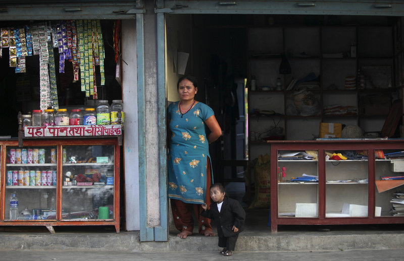 Khagendra Thapa Magar stands with his mother outside their home Wednesday in Pokhara, Nepal. Thapa is likely to be declared the shortest man in the world today after official measurements.