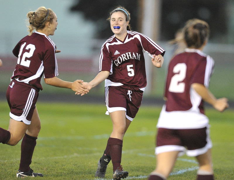 Kali St. Germain, center, gets congratulated by Audrey Adkison, left, and Sierra Peters after scoring Gorham s first goal during an SMAA girls soccer game Wednesday night against South Portland. The Rams improved to 9-3 with a 3-0 victory.