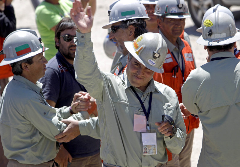 Chilean mine rescue worker Manuel Gonzalez, the first rescuer to reach the trapped miners, waves after a news conference at the San Jose mine on Thursday.