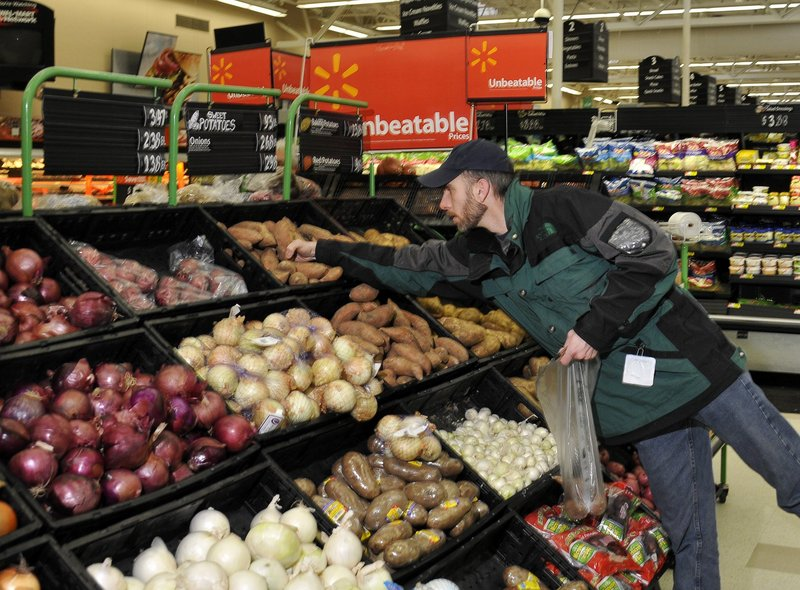 Chip DeLorenazo of Newcastle reaches for sweet potatoes in the Walmart Superstore in Augusta. More than half of Wal-Mart's $405 billion in annual revenue is from food.